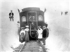 Black and white image of Ladies dressed in summer white, men in straw hats in front of train