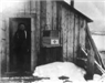 Soldier stands in doorway to office by railroad