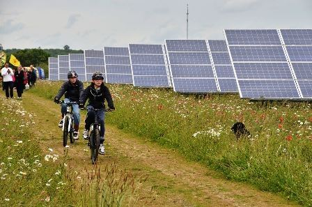 People Biking next to Solar Panels