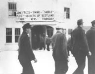 Black and white image of POWs in line passing movie theater