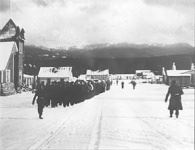 Black and white image of POWs marching in line in snow